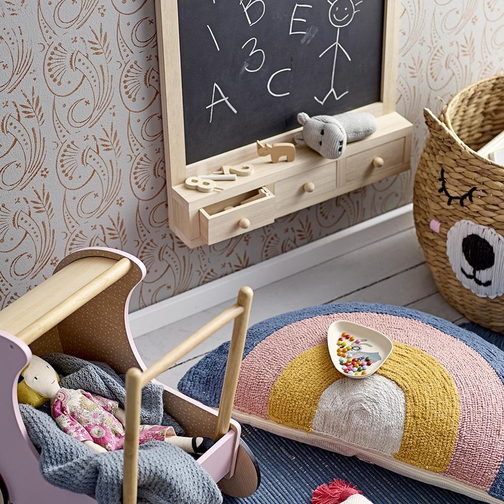 kids accessories in kids playroom: cushion, pram, doll, basket, chalkboard