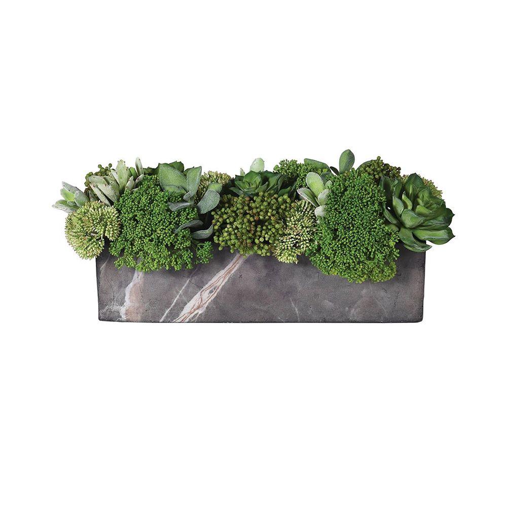 a green botanical arrangement with a grey marble pot